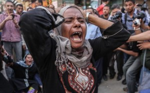 A woman cries as the new military-backed government in Egypt orders 683 people to be executed via mass trial.
